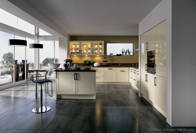 A modern kitchen with cream cabinets, gray tile floors, and a wide view of the outdoors.