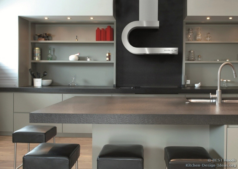 A uniquely shaped stainless steel range hood with a built-in shelf