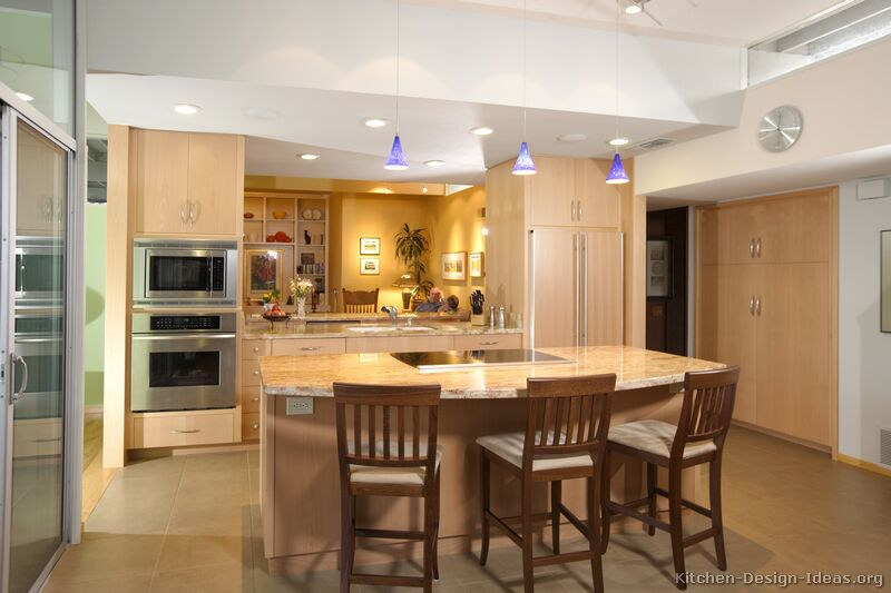 A luxury kitchen with lots of natural light, an open-plan design, and light wood kitchen cabinets.