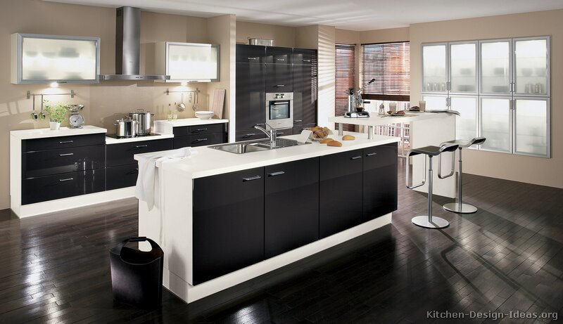 A black and white kitchen (by ALNO) with a bi-level island and espresso hardwood floors