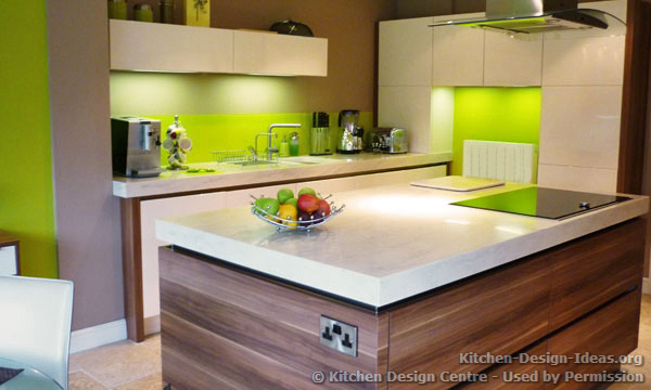 Modern kitchen with white cabinets, a rich wood island, and a vibrant green glass backsplash