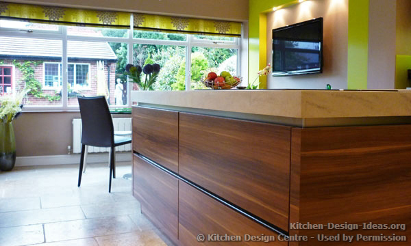 The open plan kitchen features bright green colors and large windows overlooking the garden