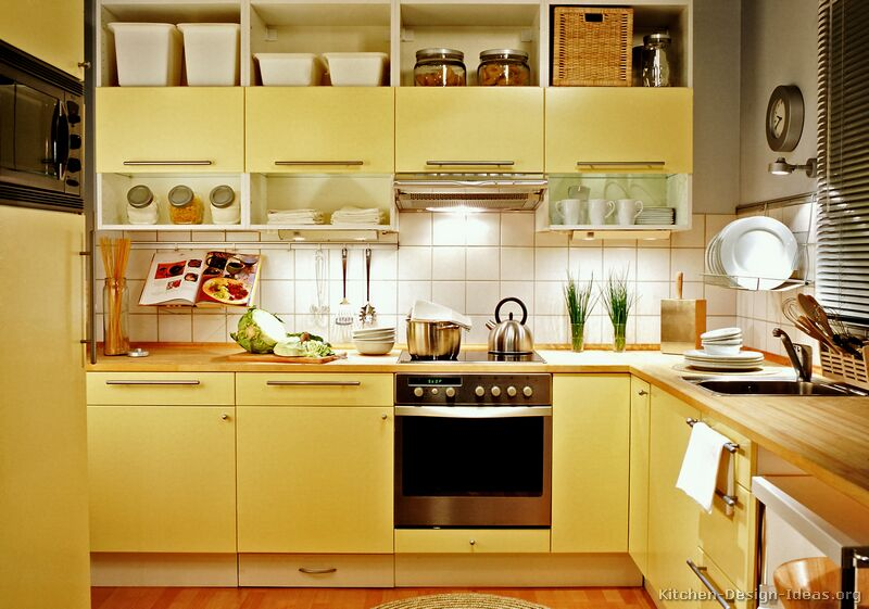 Modern yellow kitchen with butter-toned cabinets, butcher block countertops, and open shelves