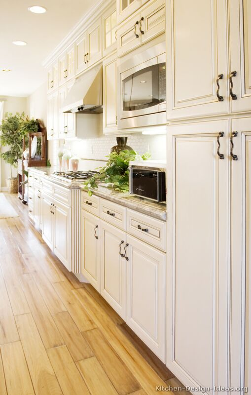 Antique white kitchen with wood floors and an island sink for White kitchen cabinets with hardwood floors