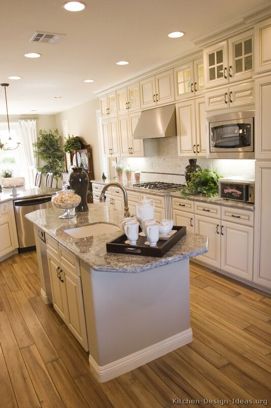 This brightly lit kitchen features antique white kitchen cabinets