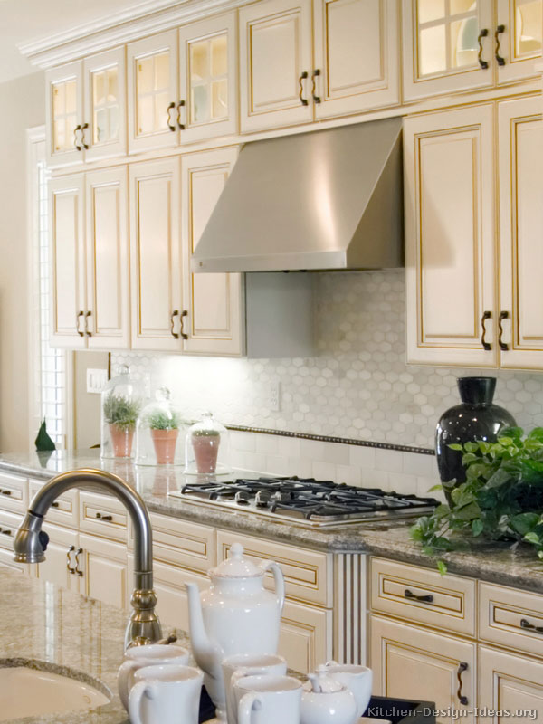 Antique White Kitchen with a Gas Cooktop, Stainless Steel Hood, and Glass Cabinets