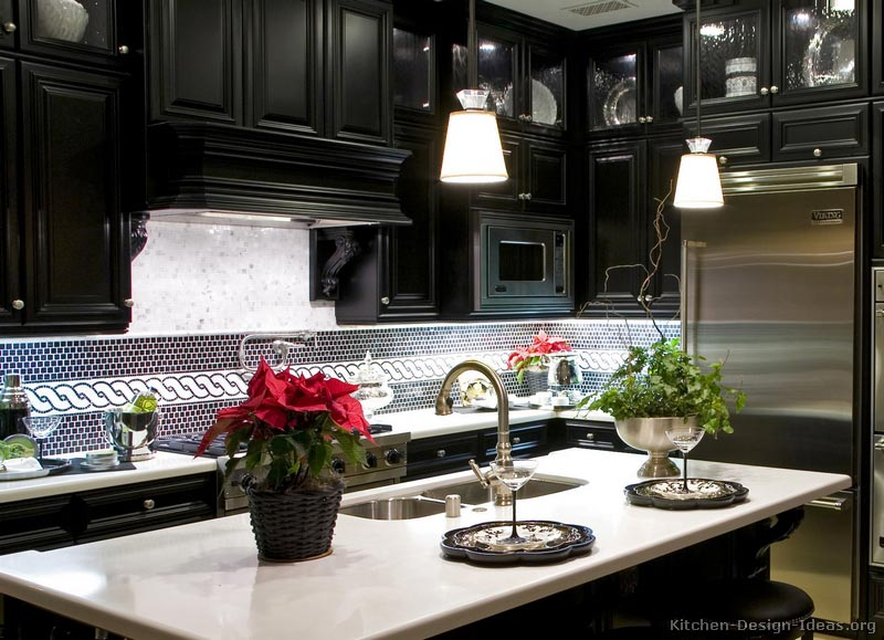 This black kitchen features a custom wood range hood and tile backsplash