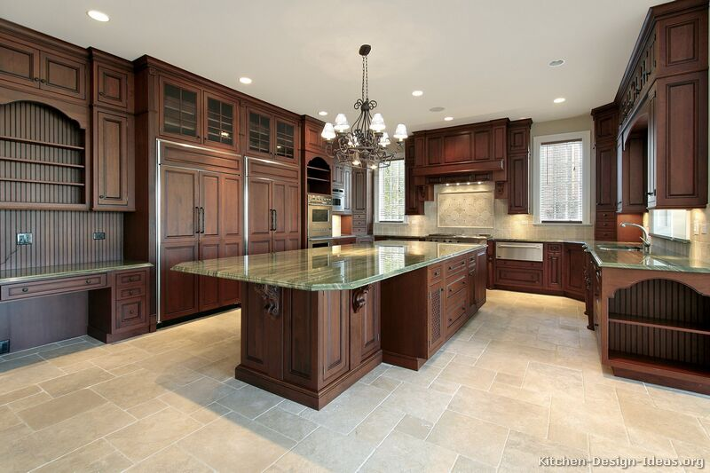Luxury kitchen with dark cherry cabinets, green granite, travertine floors, a large island, and two refrigerators