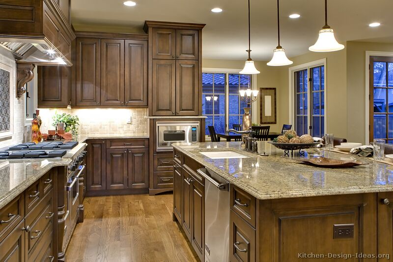 Luxury kitchen with chocolate stained cabinets, hardwood floors, and a large island