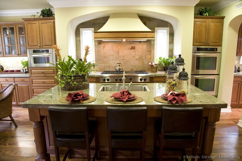 This luxury kitchen has a warm color scheme, a large island, and beautiful Seafoam Green granite countertops.