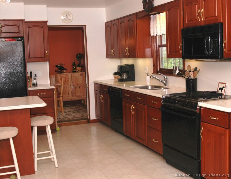 Cherry cabinets with black appliances for Traditional kitchen appliances