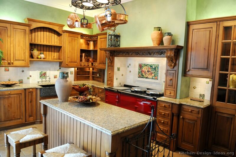 Traditional Italian kitchen with golden-brown cabinets, green walls, and a red AGA stove