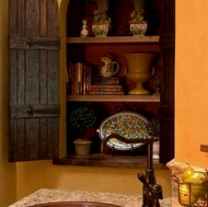 An arched wall niche with old wood doors and antique hinges.