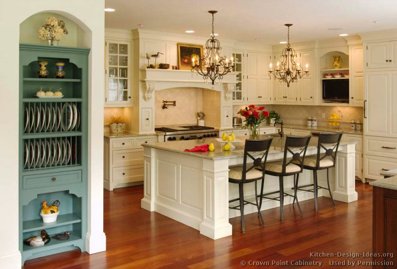 a victorian kitchen with creamy white cabinets a mantel wood hood and a large