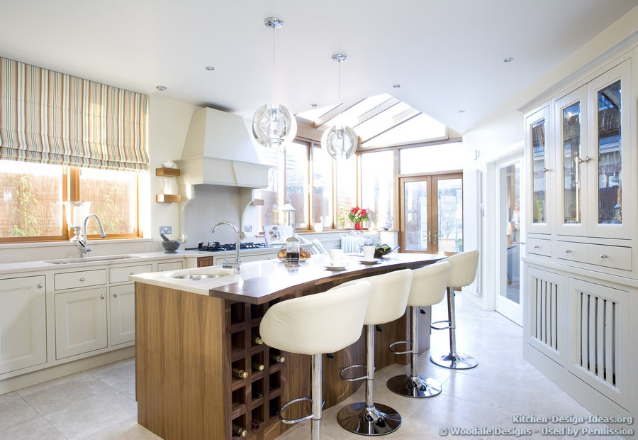Kitchen Color Trends: Natural light floods into this luxury kitchen, illuminating the soft white cabinets and walnut wood island.