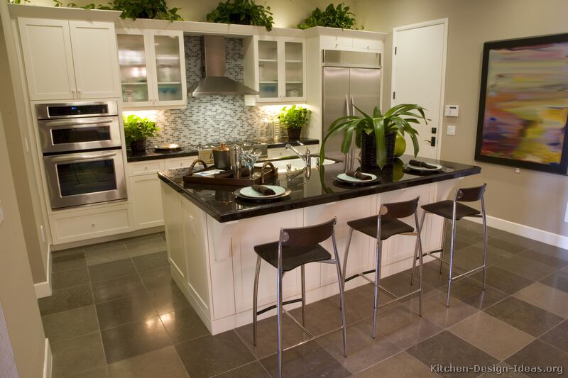 A transitional kitchen design with white cabinets, a blue glass tile backsplash, gray floors, and black countertops
