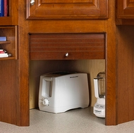 An appliance garage hides your appliances on the countertop behind a wood door.